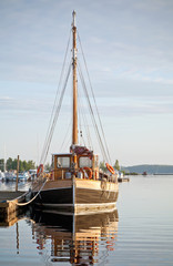 Old fashioned wooden yacht moored in small European marina