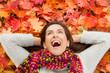 Frau im Herbst liegt auf bunten Blättern