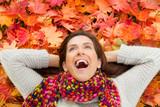 Fototapety Frau im Herbst liegt auf bunten Blättern