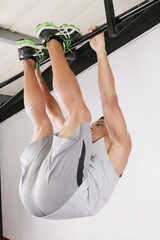 The sportsman the guy, carries out difficult exercise, sports gy