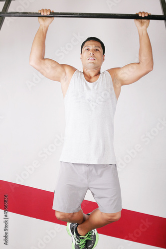 Strong man doing pull ups on a bar in a gym in the background.