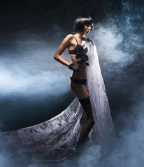 Fashin shoot of a brunette in black lingerie holding a silk cape