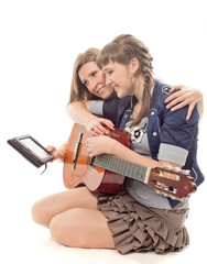 The woman shows the girl with a guitar a tablet computer