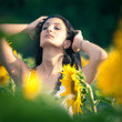 Young beautiful woman in a sunflower field with white dress.