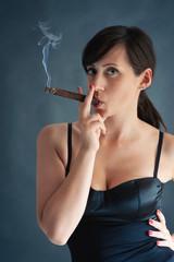 Woman smoking cigar. Studio fashion photo.
