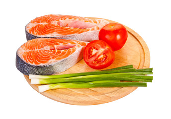 Two raw salmon steaks with tomatoes, lime  and green onion on th