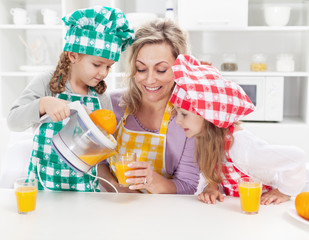 Girls and their mother making fresh fruit juice