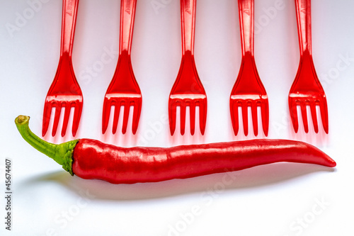 Red hot chili peppers with red table forks