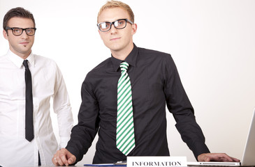 Young attractive male receptionists at information desk