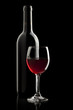 Elegant red wine glass and a wine bottle in black background