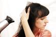 The woman dries hair the hair dryer