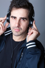 Young casual man listening to music with headphones