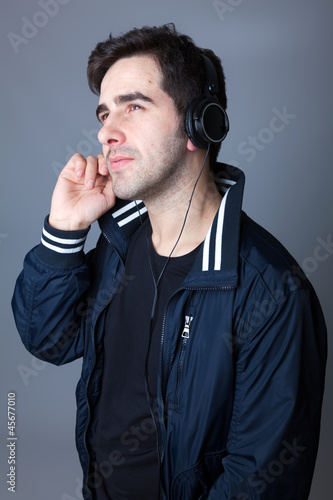 Smiling young casual man listening to music with headphones