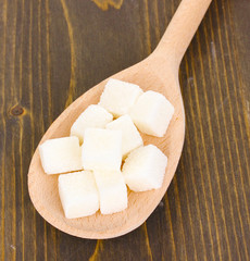 White sugar in spoon on wooden background