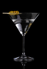 Martini glass and olives isolated on black