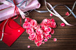 Present with petal from flowers as a heart  on wooden table
