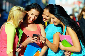 group of female students chatting in social network on phone