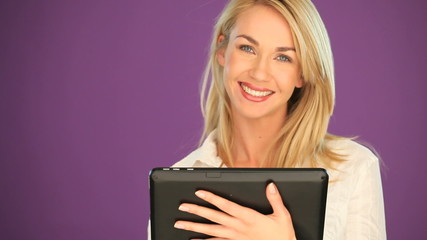 Happy blonde student working on a tablet