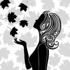 Silhouette of young woman with flying leaves