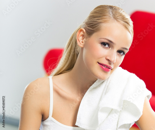 Cheerful woman in fitness wear with towel, at home