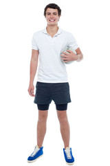 Energetic football player holding ball tightly