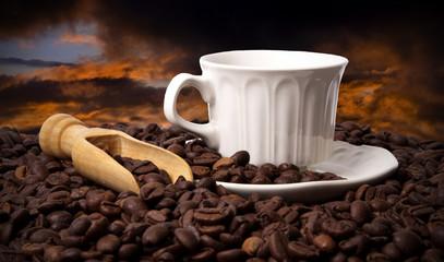 taza de café con granos y puesta de sol