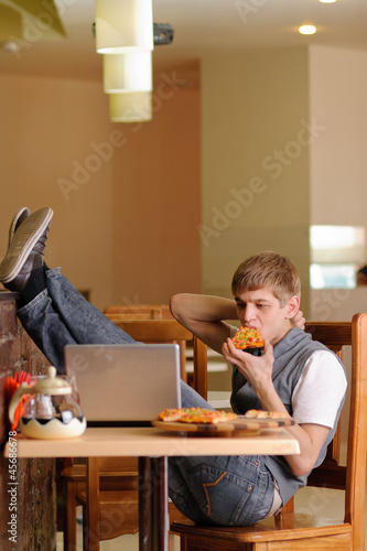 Male Student in pizzeria with Laptop. Indoor shot