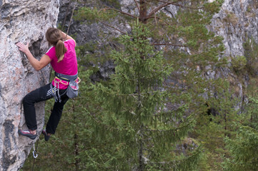 Young woman climbing the rock