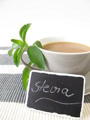 Milchkaffee mit Stevia und beschrifteter Tafel