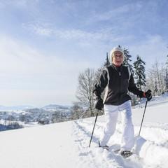 ältere Frau beim Wandern im Schnee