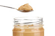 Delicious peanut butter in jar and spoon isolated on white