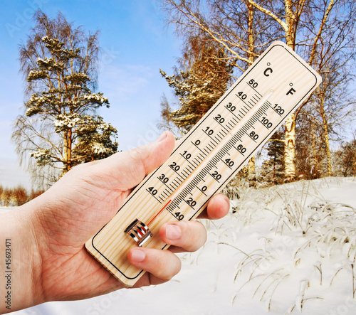 hand holding a thermometer with low against the cold of the wint