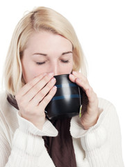 Young blonde woman drinks a cup of tea - isolated