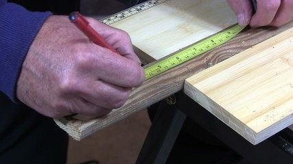 Man drilling a large hole in a piece of wood.