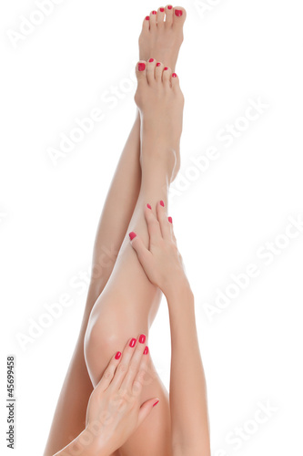 Beautiful female crossed legs and hands, isolated on white