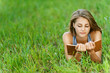 young woman-student reading book on grass