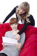 young beautiful blond and red haired girls on red sofa show lett
