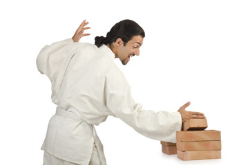 Karate man breaking bricks on white