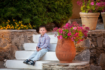 Boy is sitting on the ledder in a greek garden