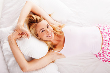 Smiling woman lying in her bed