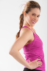 Happy young woman in pink and black fitness outfit.