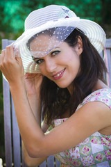 beautiful young brunette in a summer garden with white hat