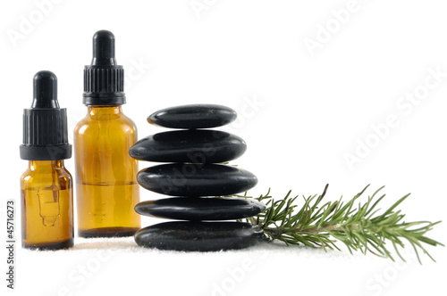 Fresh rosemary, essential oil and black stone