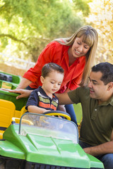 Young Mixed Race Boy Enjoys Toy Tractor with Parents