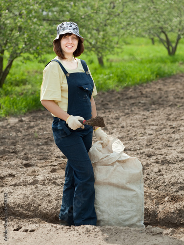Female gardener fertilizes  soil