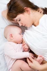 close-up portrait of mother breast feeding her baby infant
