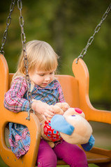 Adorable girl swing with plush toy on playground in park