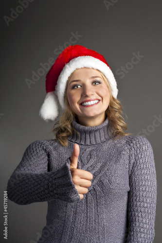 Happy smiley girl in santa hat showing thumbs up