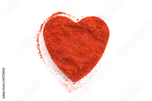 Pile of ground Paprika isolated in heart shape on white backgrou