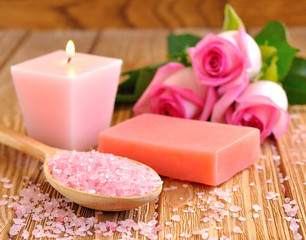 Sea salt, rose, soap and a burning candle on a brown table